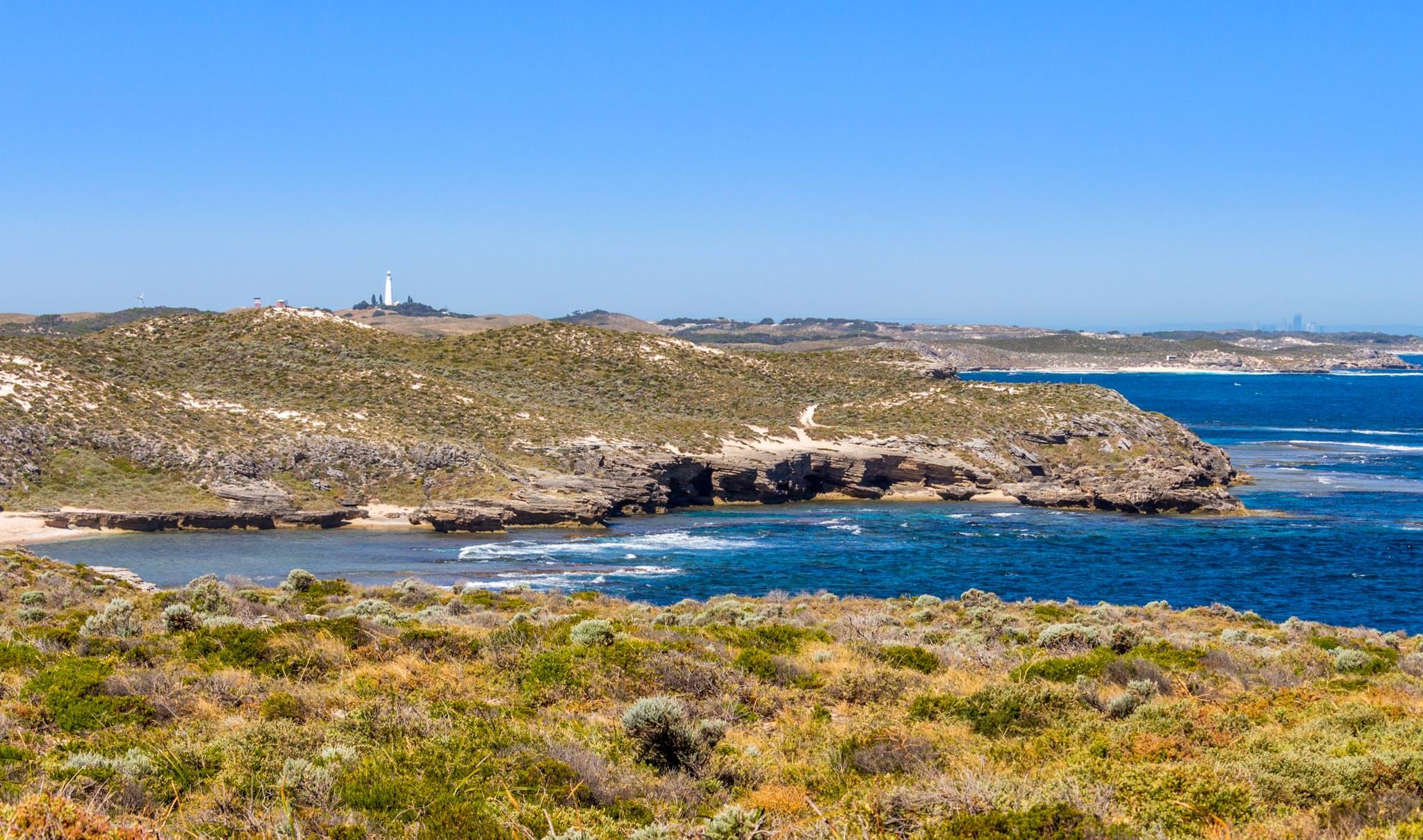 Südküste von Rottnest Island mit Wadjemup Leuchtturm und Perth Skyline im Hintergrund